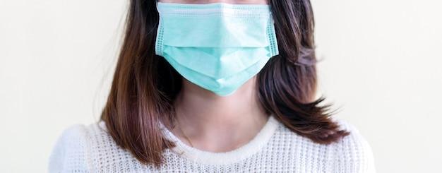 Joven y bella mujer asiática que muestra cómo usar una máscara médica o que muestra cómo usar correctamente la máscara quirúrgica de higiene paso a paso sobre fondo blanco