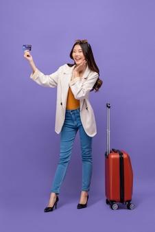 Joven y bella mujer asiática sonriente turista con equipaje mostrando la tarjeta de crédito en la mano