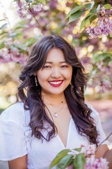 Una joven y bella mujer asiática con un vestido blanco camina en un parque de flores