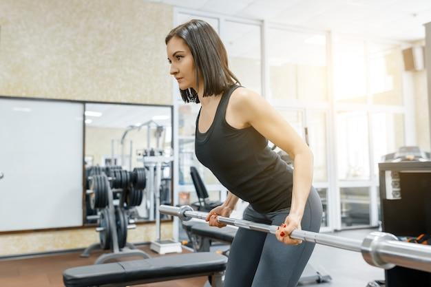 Joven y bella mujer atlética morena haciendo ejercicios de fitness en el gimnasio