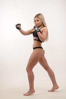 Joven y bella mujer de boxeo sexy rubia posando con guantes en la pared blanca