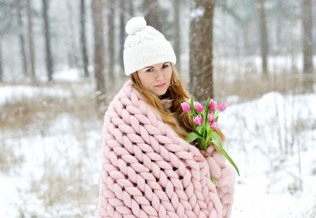 Joven y bella mujer caucásica en ropa de invierno y una manta gigante de tejer rosa pastel con flores de primavera caminando en el bosque nevado soñando con un sombrero blanco de primavera