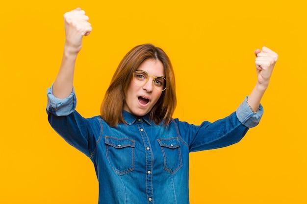Joven y bella mujer celebrando un éxito increíble como un ganador, luciendo emocionada y feliz diciendo ¡toma eso! contra el fondo amarillo
