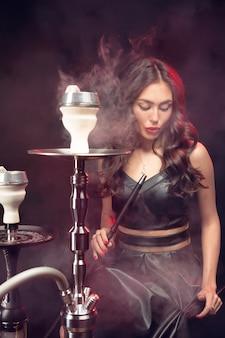 Joven y bella mujer en el club nocturno o bar fuma una cachimba o shisha