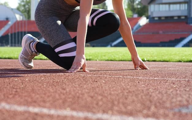 Joven y bella mujer corredor de pie al aire libre en pose de inicio en el estadio