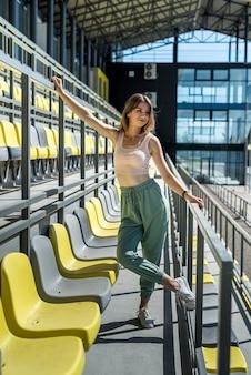 Joven y bella mujer delgada en ropa deportiva relajarse cerca de los asientos en el estadio