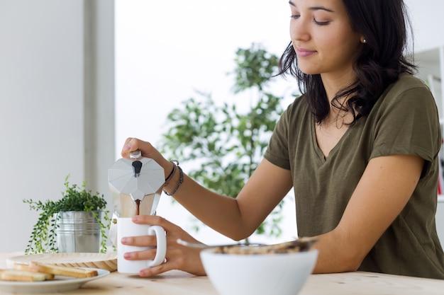Joven y bella mujer disfrutando de desayuno en casa.