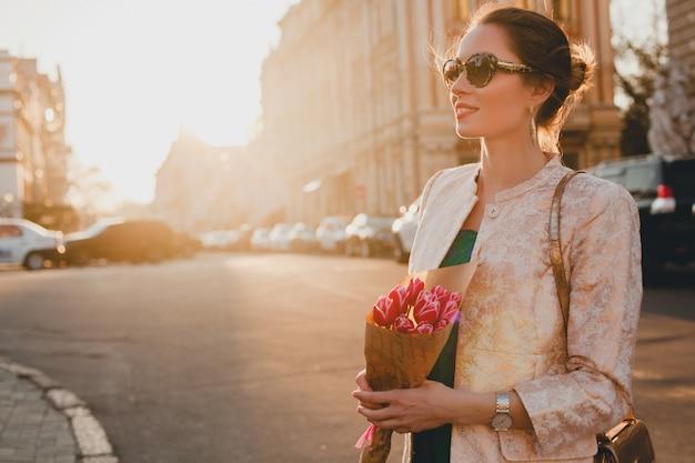 Joven y bella mujer elegante caminando por las calles de la ciudad en la puesta del sol