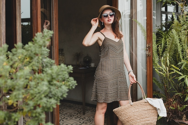 Joven y bella mujer elegante en el hotel resort, con un vestido de moda, estilo safari, sombrero de paja, vacaciones de verano, traje bohemio, bolso de playa, gafas de sol