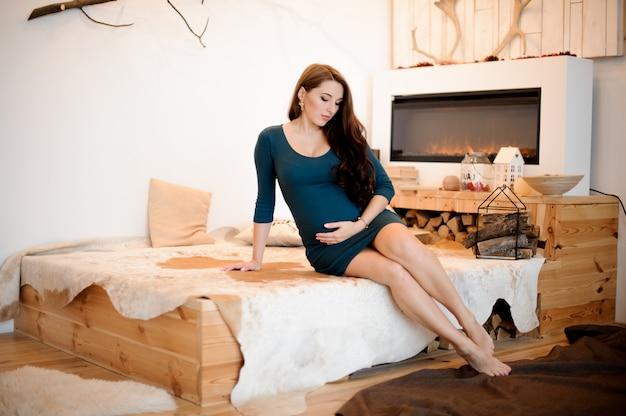 Joven y bella mujer embarazada de pelo largo sentada cerca de la chimenea