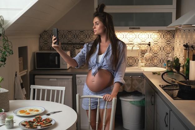 Joven y bella mujer embarazada tomando selfie en la cocina