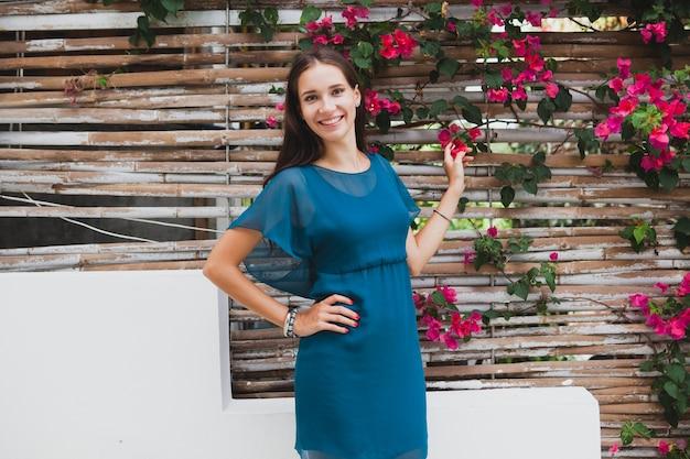 Joven y bella mujer con estilo en vestido azul, tendencia de la moda de verano, vacaciones, jardín, terraza del hotel tropical, sonriendo