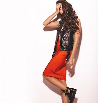 Joven y bella mujer en falda roja de verano de moda y chaqueta de cuero negro.