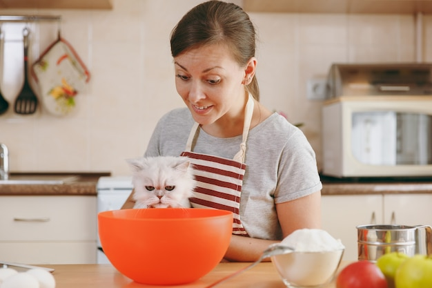 La joven y bella mujer feliz con un gato persa blanco prepara masa para pasteles con tableta en la mesa de la cocina. cocinar en casa. prepara comida.