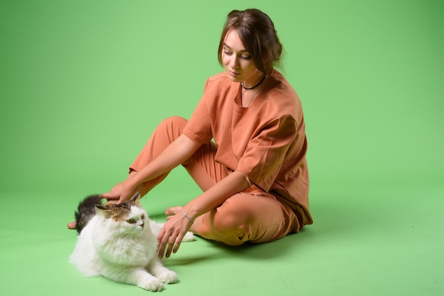 Joven y bella mujer con gato persa