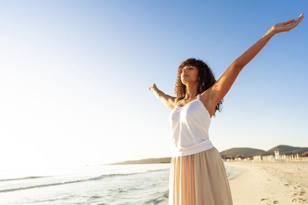 Joven y bella mujer hispana negra rizada en vestido boho con los brazos abiertos inspirados en la naturaleza