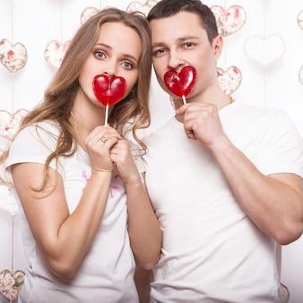 Joven, bella mujer y hombre enamorado en el día de san valentín con dulces
