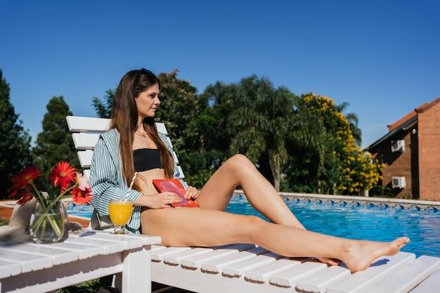 Joven y bella mujer joven delgada relajándose en una tumbona junto a la piscina