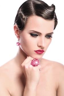 Joven y bella mujer con joyas rojas