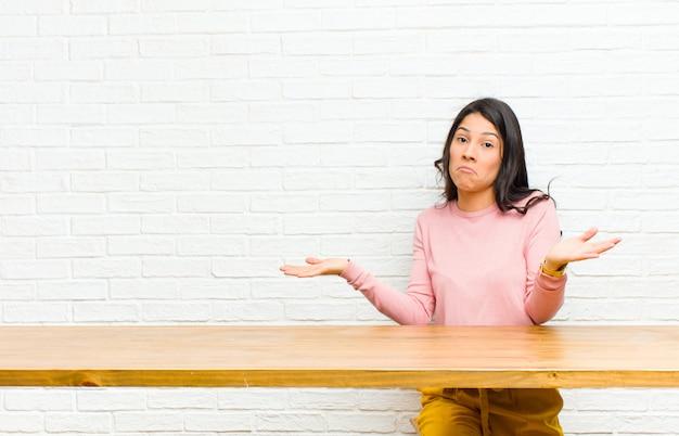 Joven y bella mujer latina que se siente confundida y confundida, insegura sobre la respuesta o decisión correcta, tratando de elegir sentarse frente a una mesa