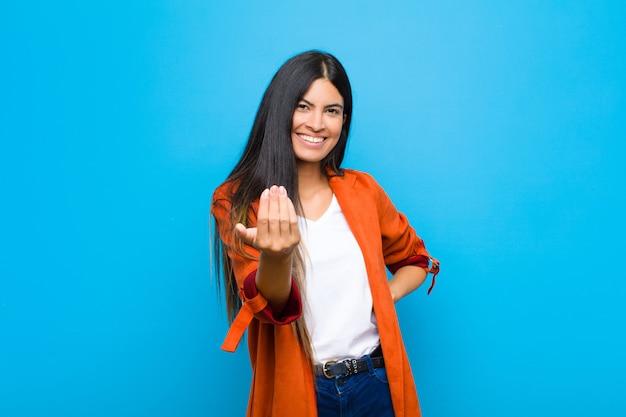 Joven y bella mujer latina que se siente feliz, exitosa y segura, enfrenta un desafío y dice ¡adelante! o darle la bienvenida contra la pared plana