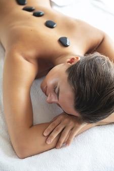 Joven y bella mujer durante el masaje con piedras calientes