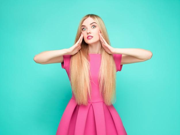 La joven y bella mujer en mini vestido rosa posando en el estudio