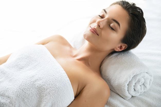 Joven y bella mujer está mintiendo y relajándose después de una sesión de masaje