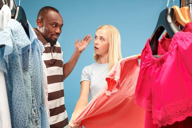 La joven y bella mujer mirando vestidos y probándose mientras elige en la tienda