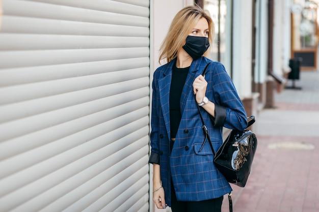 Joven y bella mujer de moda en gafas de sol con mochila en la cara máscara de contaminación para protegerse del coronavirus caminando en la ciudad