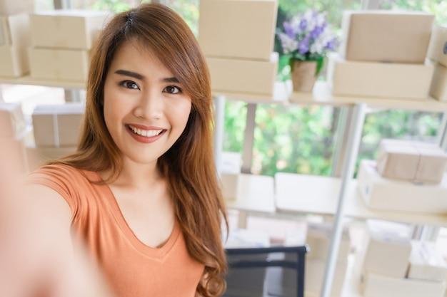 Joven y bella mujer de negocios asiática feliz en ropa casual con cara sonriente es selfie en su oficina en casa con caja de paquete en el estante, pyme, compras en línea