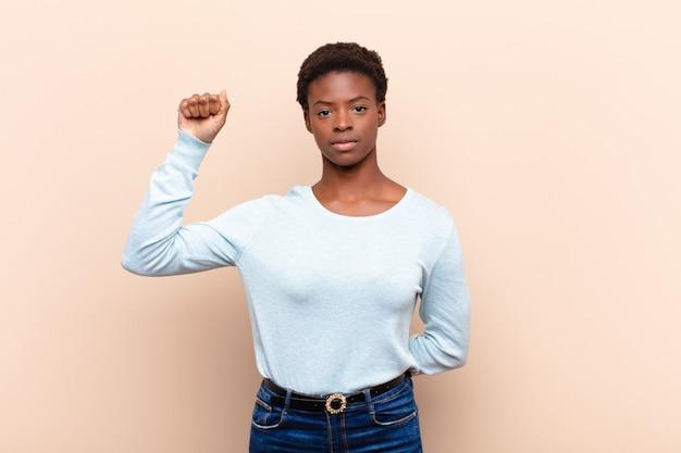 Joven y bella mujer negra que se siente seria, fuerte y rebelde, levantando el puño, protestando o luchando por la revolución