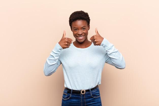 La joven y bella mujer negra sonríe ampliamente, feliz, positiva, segura y exitosa, con ambos pulgares arriba