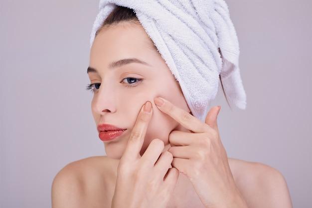 La joven y bella mujer presiona el acné en una mejilla.