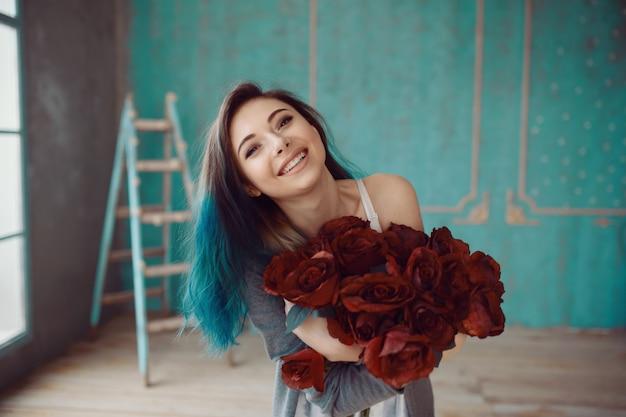 Joven y bella mujer con ramo de rosas