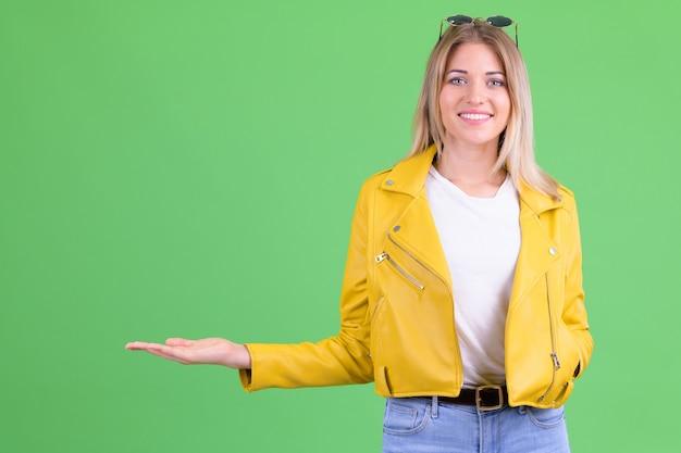 Joven y bella mujer rebelde con cabello rubio contra chroma key en verde