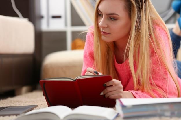 Joven y bella mujer rubia se encuentran en el piso leer libro