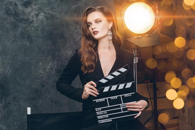 Joven y bella mujer sexy con estilo en el cine entre bastidores, sosteniendo la chapaleta de la película