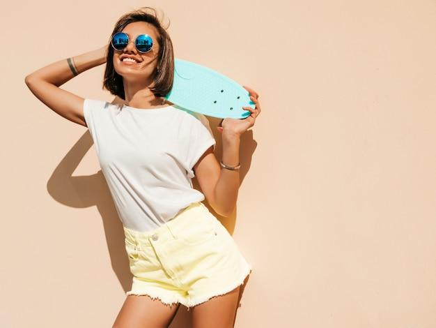Joven y bella mujer sexy hipster sonriente en gafas de sol. chica de moda en camiseta y pantalones cortos de verano. mujer positiva con patín azul centavo posando en la calle cerca de la pared