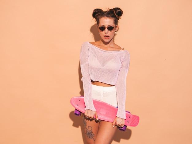 Joven y bella mujer sexy hipster sonriente en gafas de sol. chica de moda en verano tema punto cardigan, pantalones cortos. mujer positiva volviéndose loca con monopatín rosa centavo, aislado en la pared de color beige. dos hor