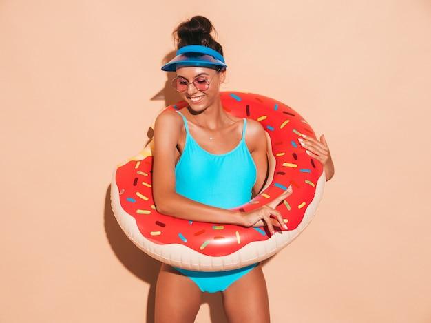 Joven y bella mujer sexy hipster sonriente en gafas de sol. chica en traje de baño de verano con colchón inflable donut lilo. mujer positiva volviéndose loca. pared beige cerca de gorra de visera transparente