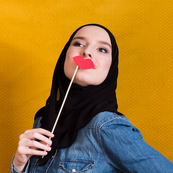 Joven y bella mujer sosteniendo un fotomatón en forma de labios rojos.