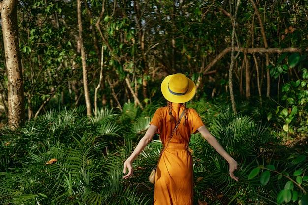 Joven y bella mujer spacetropics selva con sombrero camina parque espacial, naturalista