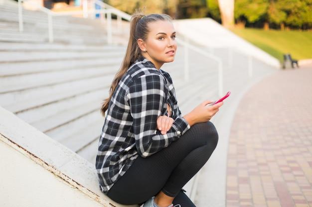 Joven y bella mujer de talla grande en camisa casual y leggings apoyado en la barandilla de la escalera mirando pensativamente a un lado con el teléfono celular en la mano mientras pasa tiempo en el parque