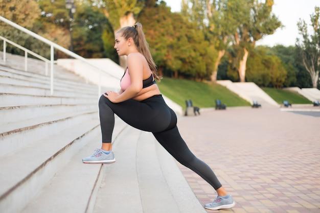 Joven y bella mujer de talla grande en la parte superior del deporte y leggings soñando estirando en las escaleras en el parque de la ciudad al aire libre
