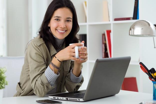 Joven y bella mujer usando su computadora portátil en casa.