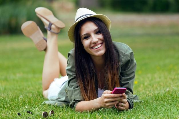 Joven y bella mujer utilizando su teléfono móvil en el parque.