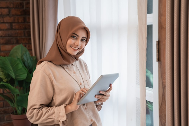 Joven y bella mujer con velo sosteniendo tableta y mira la cámara de pie cerca de las ventanas de cortinas