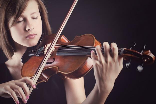 Joven y bella mujer con un violín