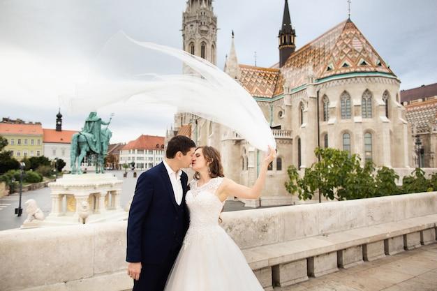 Joven y bella pareja elegante de recién casados besándose por el bastión de los pescadores en budapest, hungría